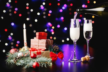 New Year and Christmas decor. Someone pours champagne in the glasses on a table with presents