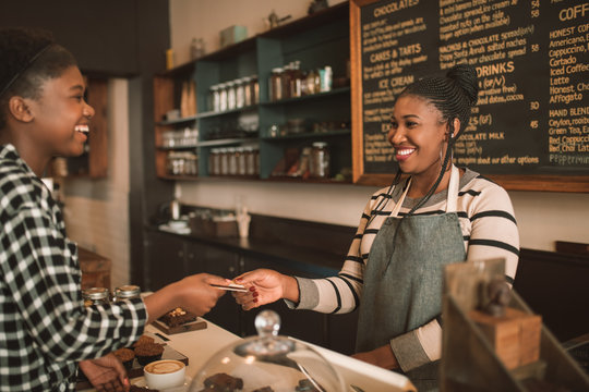 Smiling woman giving her credit card to a cafe barista