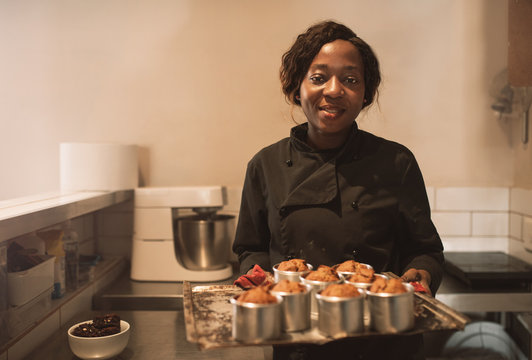 Smiling baker holding a tray of muffins in her kitchen