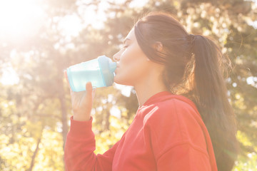 Athletic woman in sporty red clothes drinking water while jogging. Portrait, close-up in the sunset sunlight. silhouette of girl drinking water outdoor