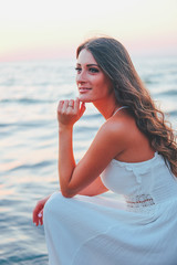 Romantic feminine woman in white dress waiting at the shore