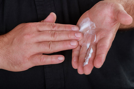 Cosmetician man hand with cream on hands