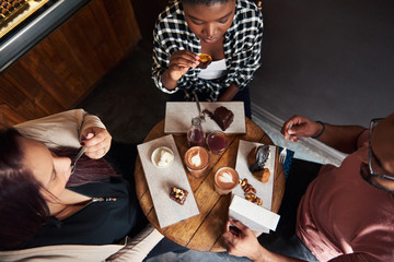 Friends sitting at a cafe table enjoying delicious desserts together