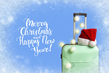 Plastic suitcase, Santa Claus hat and garland on blue background with snow. Concept of travel to visit friends and relatives on Christmas holidays. Add text Merry Christmas and Happy New Year