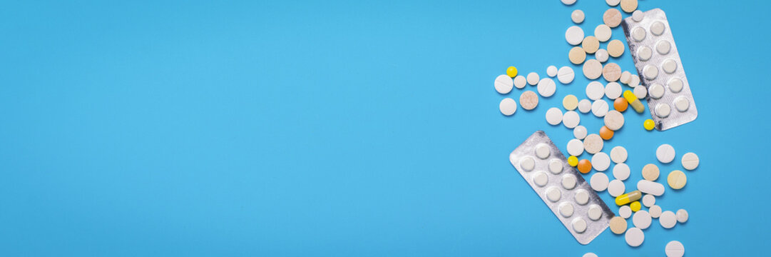 Pills of different colors on a blue background. Concept of the pharmaceutical industry, medicine, treatment and recovery after illness. Banner. Flat lay, top view