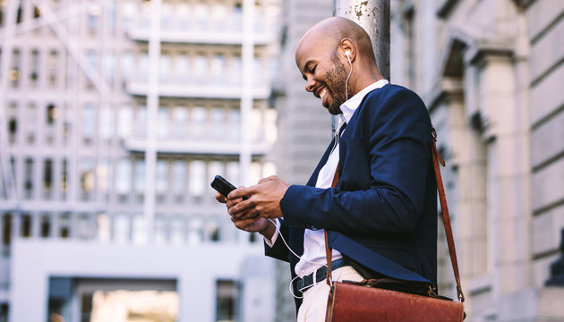 African businessman walking outdoors with mobile phone