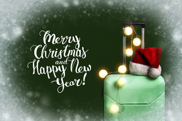 Plastic suitcase, Santa Claus hat and garland on dark green background with snow. Concept of travel to visit friends and relatives on Christmas holidays. Add text Merry Christmas and Happy New Year