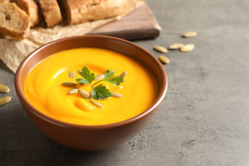 Delicious pumpkin cream soup in bowl on gray background. Space for text