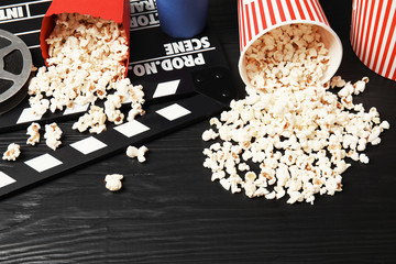 Tasty popcorn and clapperboard on wooden table. Cinema snack