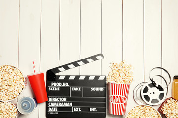 Flat lay composition with popcorn, cinema clapperboard and space for text on white wooden background