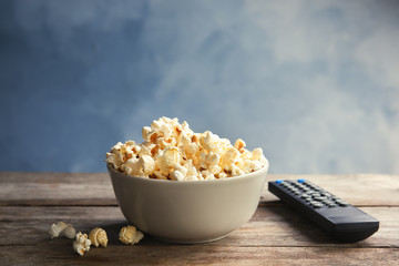 Bowl of popcorn and TV remote on table against color background. Watching cinema