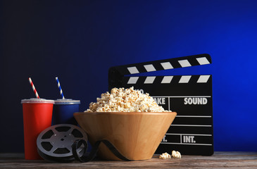 Composition with popcorn, cinema clapperboard and film reel on table against color background