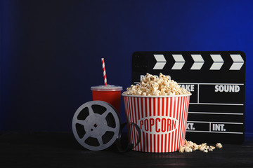 Composition with popcorn, cinema clapperboard and film reel on table against color background. Space for text