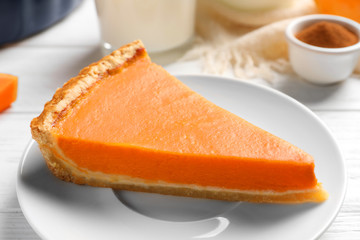 Plate with piece of fresh delicious homemade pumpkin pie on wooden table