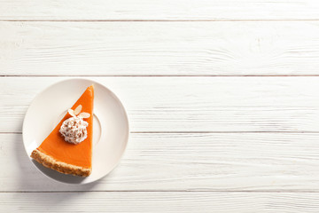 Plate with piece of fresh delicious homemade pumpkin pie on wooden background, top view. Space for text