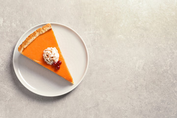 Plate with piece of fresh delicious homemade pumpkin pie on gray background, top view. Space for text