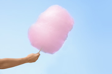 Woman holding cotton candy against blue sky