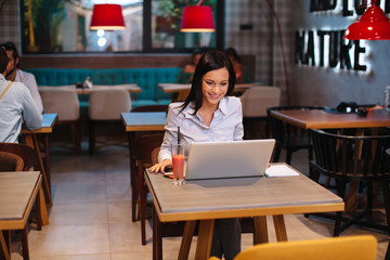 Young happy business woman using a laptop in a coffee shop