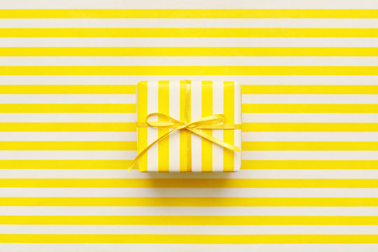 Yellow gift box on white and yellow striped wrapping paper. Minimal geometric background.