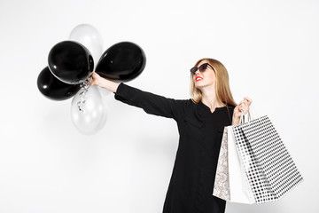 Elegant woman wearing sunglasses in a black dress and red lips, in the hands of bags for shopping and black balls, in anticipation of Black Friday on a white background