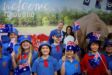 Children from Dubbo Public School wave Australia's national flags while waiting for Britain's Prince Harry and his wife Meghan, Duchess of Sussex, to arrive at Dubbo airport, Dubbo