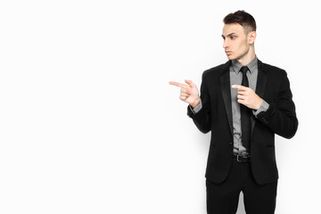 Portrait of an elegant man in a black suit, confident, pointing to an empty copy of the space isolated on a white background