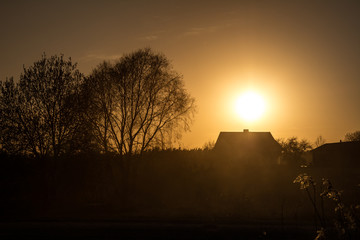 Silhouette of a house and trees near empty road with dust in countryside  at sunset. Sunset colors. Clear sky.