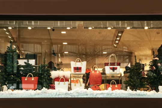 Shop window decorated in Christmas style. Christmas and New Year sales. Many different handbags and other items are sold in stores.