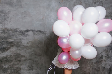 hide behind a large bunch of balloons. Girl and a lot of pink balloons