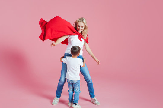 Mom is a superhero. Fun family, a young blond woman in a red Cape and her son