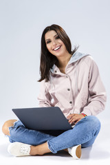 Modern Lifestyle Concepts. Happy Positive  Caucasian Brunette Girl Working with Laptop While Seating on Floor with Legs Crossed. Posing in Hoodie and Blue Jeans Against White