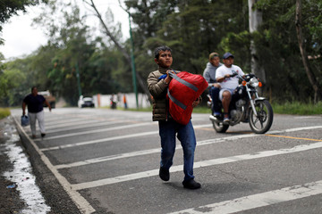 A Honduran migrant, part of a caravan trying to reach the U.S., walks as he holds a bag during a new leg of their travel in Quezaltepeque
