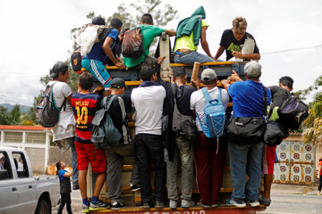 A Honduran migrant, part of a caravan trying to reach the U.S., are pictured on a truck during a new leg of their travel in Quezaltepeque