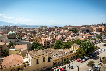 View on the city of Cagliari, the capital of Sardinia, Italy. Colorful houses and clear blue sky on a sunny day, mountains in the background.
