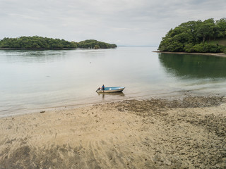 A lone fisherman prepares his small fishing boat to head out into the Gulf of Nicoya from an aerial drone