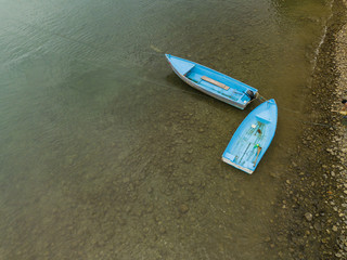 Two colorful fishing skiffs sit anchored in shallow water beach in Costa Rica taken from an aerial drone