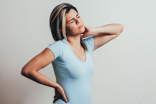 Young woman with neck pain over white background