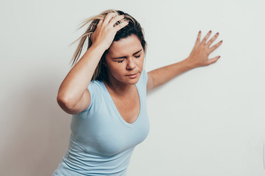 Woman suffering from dizziness with difficulty standing up while leaning on wall