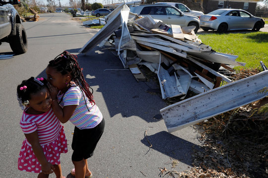 Sisters Amiyah and Ariannah whisper to each other outside their home damaged by Hurricane Michael in Springfield