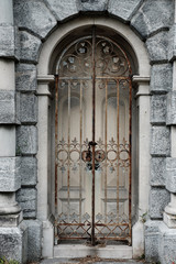 Rusting iron Gated doorway surrounded by granite archway