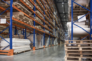 Large hall of logistic warehouse, many shelves with pallets and goods