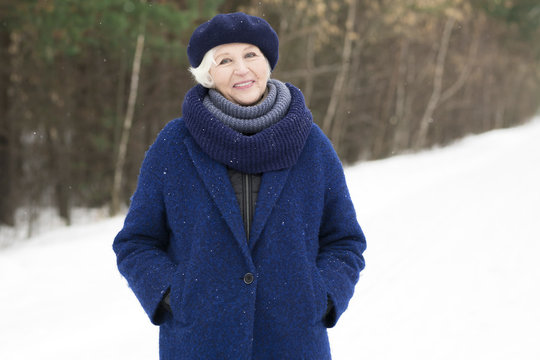 Waist up portrait of elegant senior woman posing in winter forest and smiling at camera, copy space