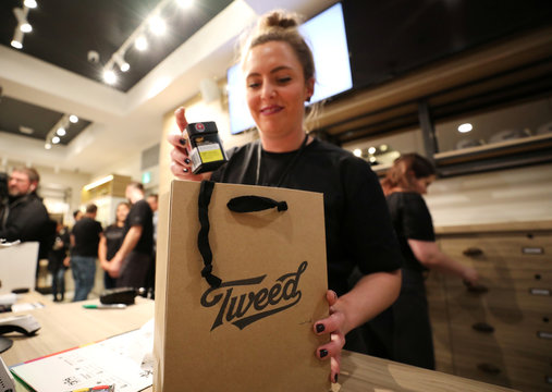 An employee packs purchases into a shopping bag after the first legal recreational marijuana sale after midnight at a Tweed retail store in St John's