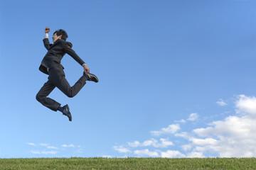 青空をバックに空中を走るスーツ姿の若いビジネスマン1人。元気・健康・発展・挑戦イメージ