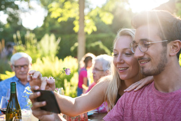 During a family bbq a young couple does a selfie on their phone