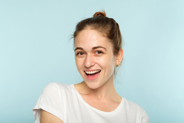 happy smiling joyful delighted woman. young beautiful brown haired girl emotional portrait on blue background. facial expression.