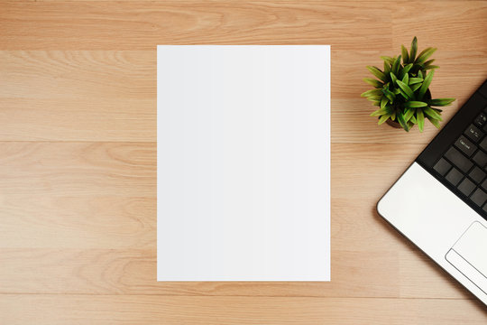 White template paper and space for text with laptop on wooden desk