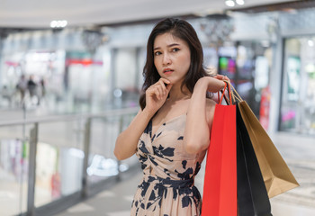 woman thinking and holding shopping bags in mall