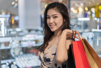 happy woman with shopping bags in mall