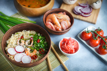 Asian food, Tom Yam and Ramen with shrimps, Thai food in wooden bowl, Egg noodles, Preparation, Chilli peppers, onion and mushrooms, Spicy, Lght gray background, Closeup, Selective focus